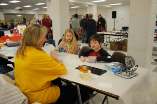 Lion's Club volunteer playing bingo at the Kids' Table