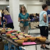 An Empty Bowls attendee looks over some of the beautiful bowls for sale at the fundraiser event.