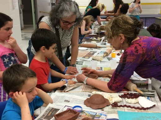 Local potter and Empty Bowls volunteer, Roberta Green helps a child with a clay project at the Empty Bowls event.