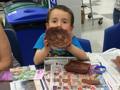 A young potter proudly displays his clay bowl.