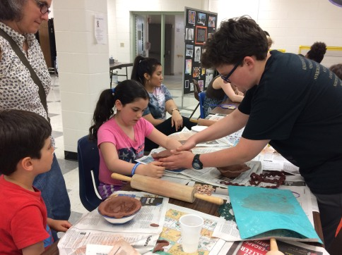 A WVHS Empty Bowls Club member helps a young potter make a clay bowl.