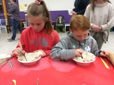 Young potters make a clay bowl.