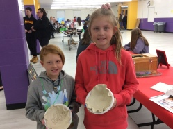 Young potters proudly display their clay bowls.