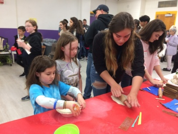 WVHS Empty Bowls Club members help young potters create clay bowls.