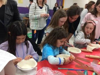 Young potters make clay bowls.