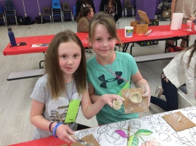 Young potters proudly displaying their miniature bowls.